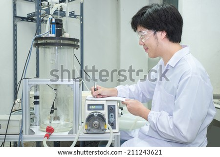 Scientist conducting research taking notes  in laboratory