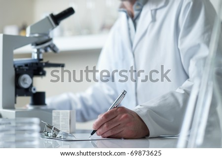 scientist conducting research with microscope selective focus - stock photo