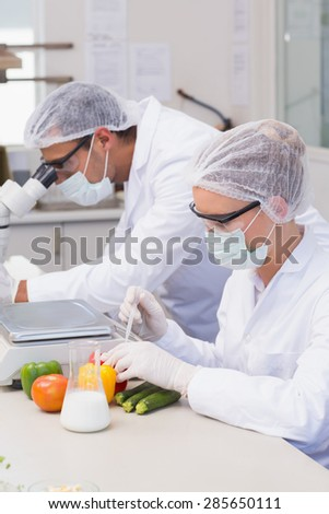 Scientist doing experimentation on vegetables in the laboratory - stock photo