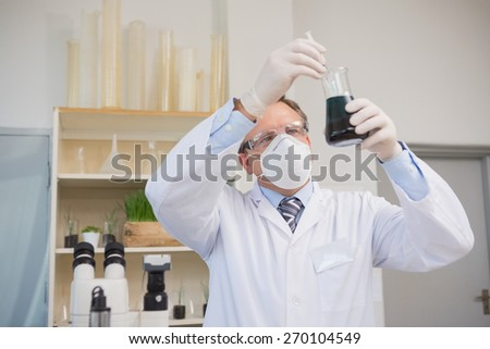 Scientist doing experimentations in flask in the laboratory - stock photo
