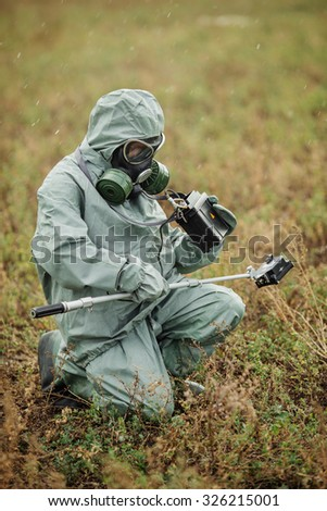 Scientist dosimetrist (radiation supervisor) in protective clothing and gas mask with geiger counter checks the level of radioactive radiation in the danger zone - stock photo