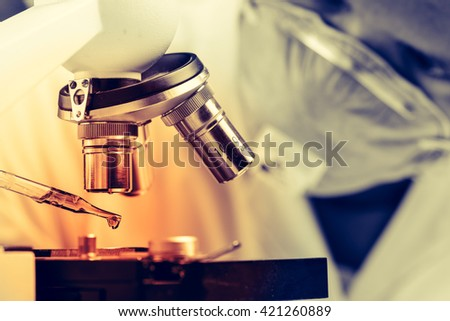 Scientist  dropping chemical liquid to microscope, Laboratory research concept - stock photo