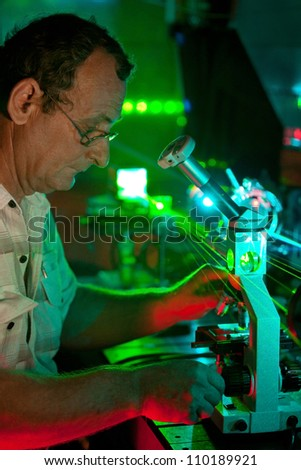 Scientist engaged in research in his lab show movement of microparticles by laser - stock photo