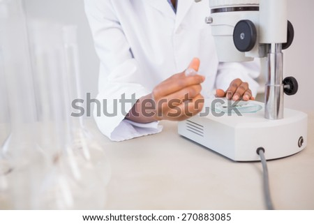 Scientist examining petri dish under microscope in laboratory - stock photo