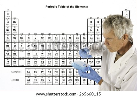 Scientist explaining a complex theory or analysis in front of the periodic table of elements - stock photo