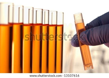 Scientist hand holding a laboratory cuvette filled with orange liquid near test tubes with chemical for an experiment in a science research lab  - stock photo