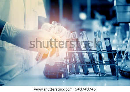 scientist hand holding laboratory test tube with soft focus
