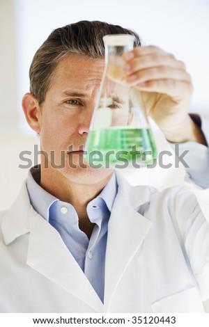 scientist holding up jar of chemicals - stock photo