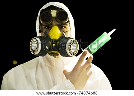 scientist in gas mask and goggles holding syringe with green substance - stock photo