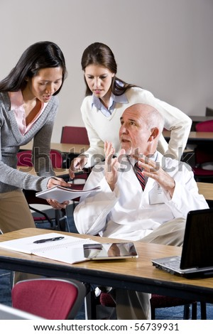 Scientist in lab coat talking to assistants in conference room - stock photo