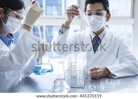 Scientist in laboratory examining liquid in Erlenmeyer flask. - stock photo