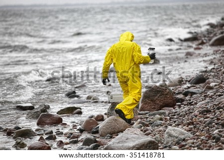 scientist in protective suit with plastic container walking in on rocky beach - back view - stock photo