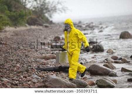 scientist in protective suit with silver case walking in water at rocky beach - back view - stock photo
