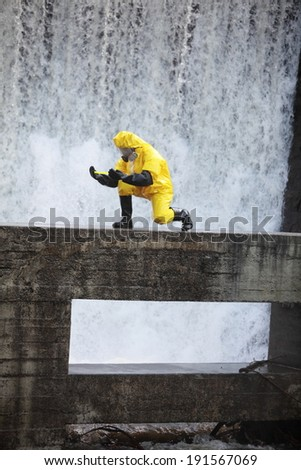 scientist in protective uniform examining toxic substance in contaminated area - stock photo