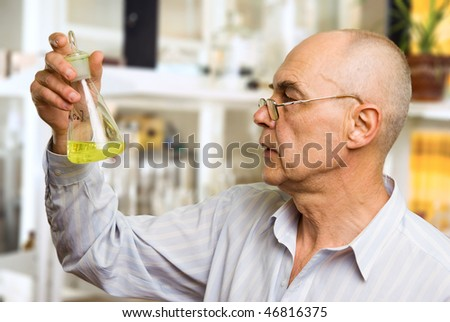 scientist in the chemical lab examines a flask with a substance