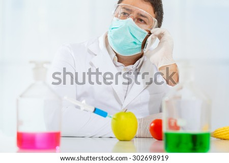 Scientist injecting chemicals into fruits and vegetables. Talking on the phone. - stock photo