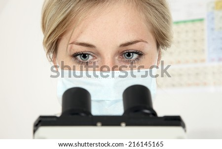 Scientist looking into microscope in laboratory