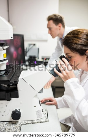 Scientist looking through a microscope at the laboratory - stock photo