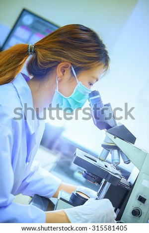 Scientist looking through a microscope in a laboratory hospital - stock photo