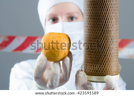 scientist shows a filter and an apple in hands - stock photo