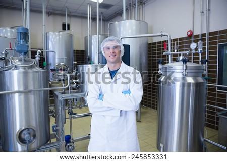 Scientist with arms crossed wearing protective glasses in the factory