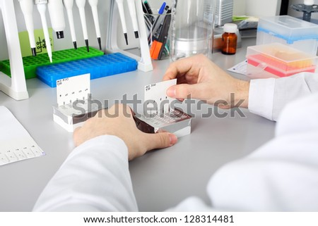 Scientist with dropper working  at the laboratory - stock photo