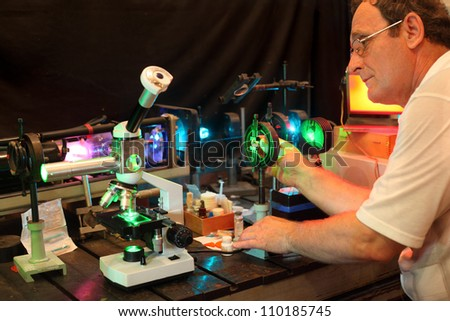 Scientist with glass demonstrate laser of microparticles - stock photo