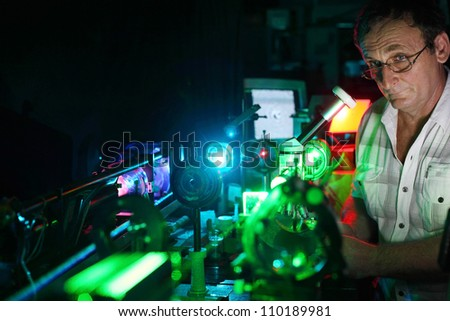 Scientist with glass demonstrate laser of microparticles, front - stock photo