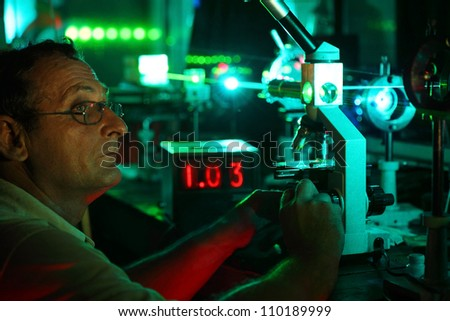 Scientist with glass demonstrate laser of microparticles near timer - stock photo