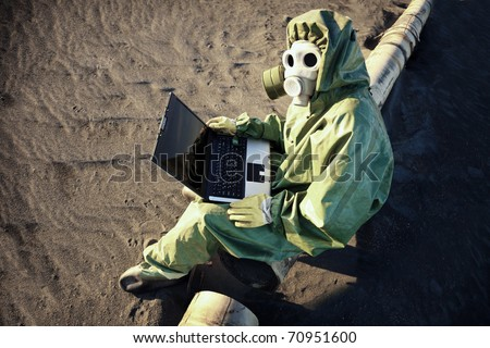 Scientist with laptop in zone of ecological disaster - stock photo