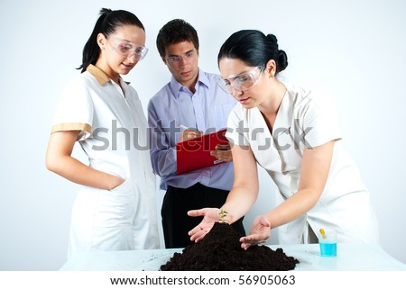 Scientist woman holding hands on soil with plant and explaining to her colleagues who listening her and taking notes.Can be a teacher with students in laboratory too. - stock photo
