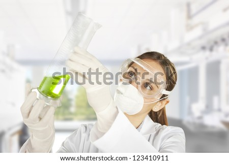 scientist woman in lab coat with chemical glassware. Portrait of a young chemist working with medicine - stock photo