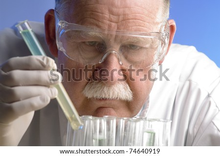 Scientist working with chemicals on blue background - stock photo