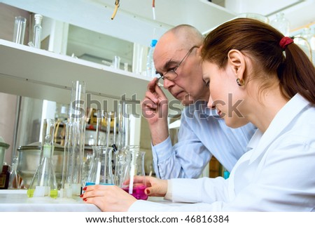 scientists conducting research in the chemical laboratory - stock photo