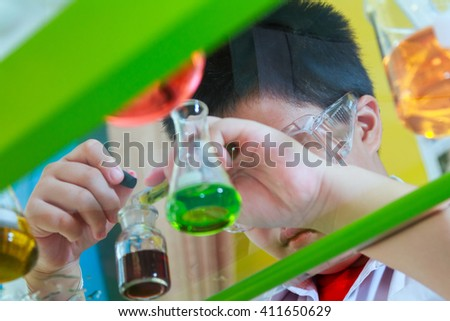 Scientists junior is a very happy or fun to make and play chemical science experiment in science class, copy space, mock-up, web template for design or decorate your content, Asia boy 10 year.