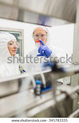 Scientists looking at beaker together at the lab - stock photo