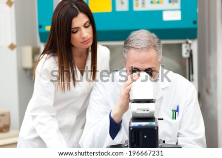 Scientists using a microscope in a laboratory - stock photo