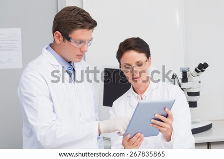 Scientists using tablet in laboratory - stock photo