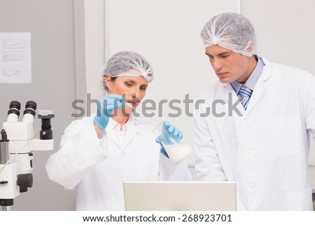 Scientists working attentively with beaker in laboratory - stock photo