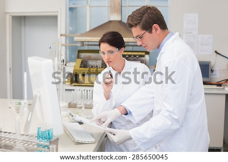 Scientists working attentively with computer in laboratory - stock photo