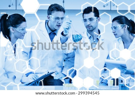 Scientists working on an experiment at the laboratory against science graphic - stock photo