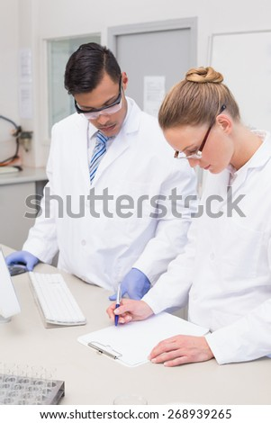 Scientists writing on clipboard in the laboratory