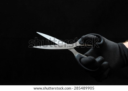 Scissors and a Hand on a Black Background - stock photo
