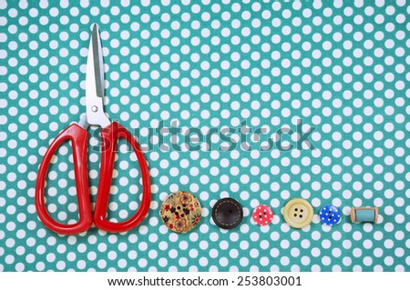 Scissors and buttons on blue polka dot fabric background - stock photo