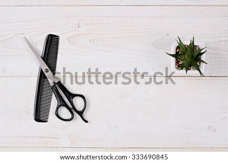 Scissors and comb on white rustic wooden background. Hairdresser salon concept. Haircut  accessories, flat lay - stock photo