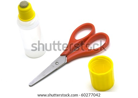 Scissors and glue over white background