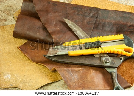 Scissors and Knife Cutter for cutting leather on  background - stock photo