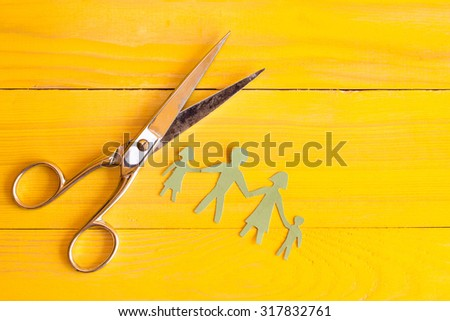 Scissors and  paper cut people on the yellow wooden surface - stock photo