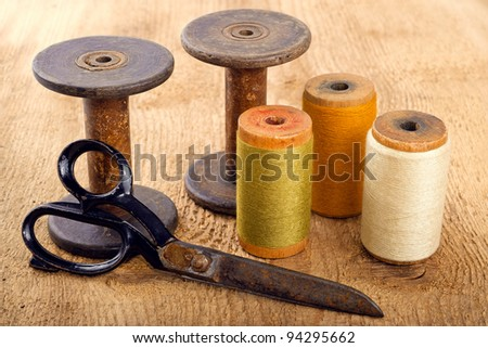 Scissors and spools  on wooden background - stock photo