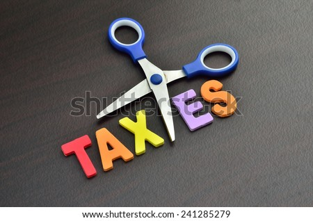 scissors and the alphabet TAXES - stock photo